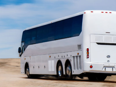 A white bus driving in the desert